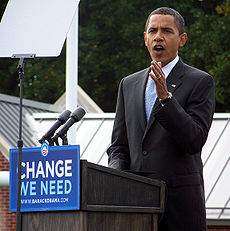 "Full body photograph of a middle-aged man wearing a black suit and a blue tie speaking in front of a teleprompter. A sign spelling ""Change we need"" is seen in the podium at which the man is speaking."